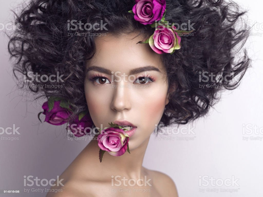 Beautiful young woman with flowers in her mouth and hair stock photo