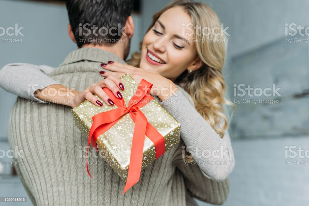 Beautiful Young Woman With Gift Box Embracing Her Boyfriend At Home Stock Photo Download Image Now Istock