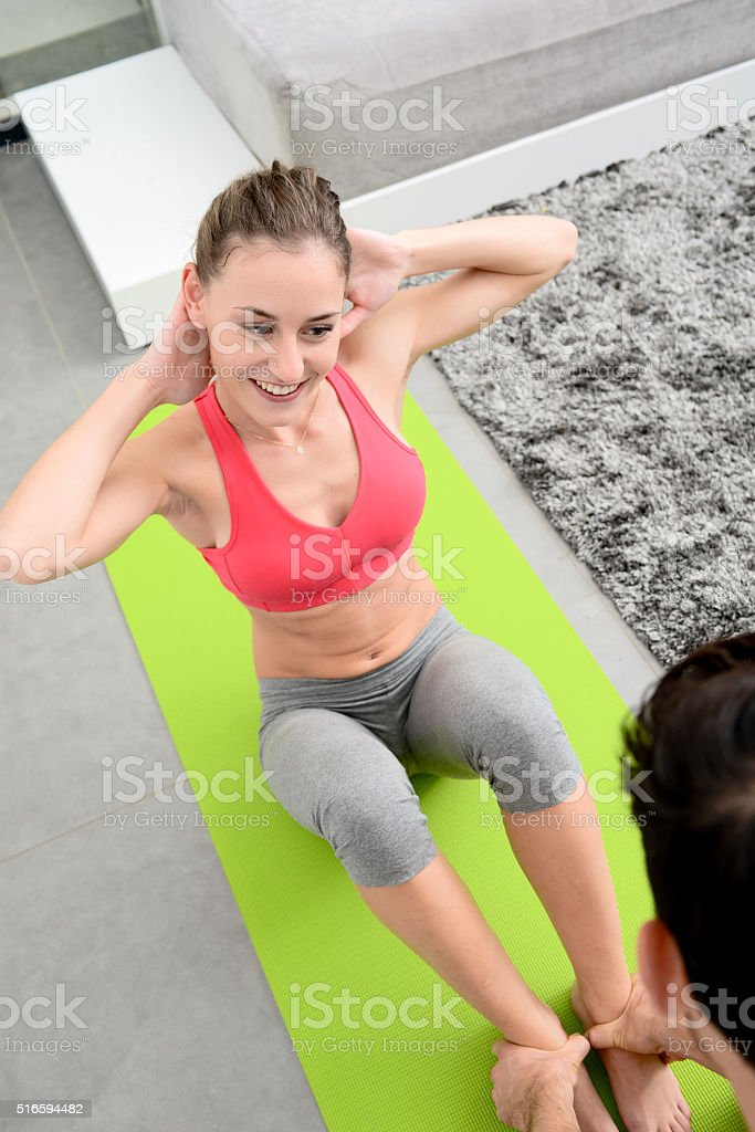 Beautiful young woman with a handsome private fitness coach at home