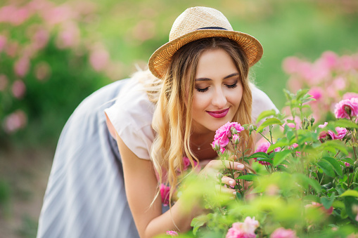 Beautiful young woman with hat is smelling roses in a garden