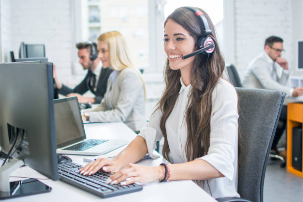 Beautiful young woman with headset working on computer while talking with client in call center. Online customer support. stock photo