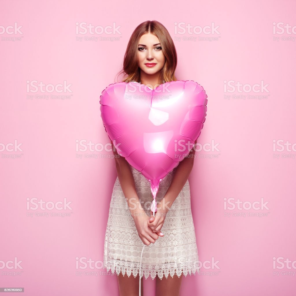 Beautiful young woman with heart shape air balloon stock photo