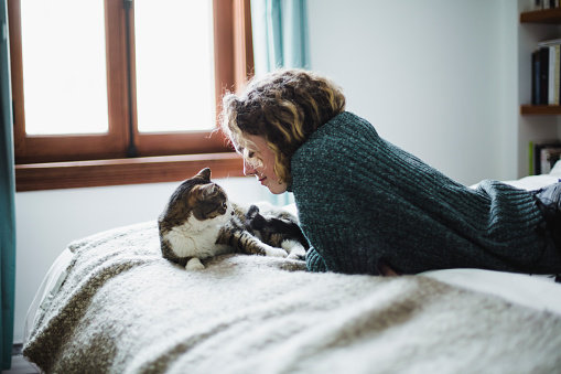 Beautiful young woman with her cat on a bed