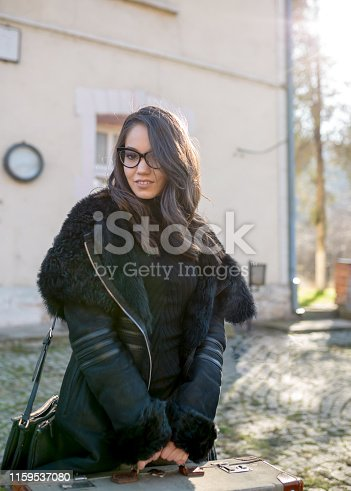Beautiful young woman with her suitcase on the train station