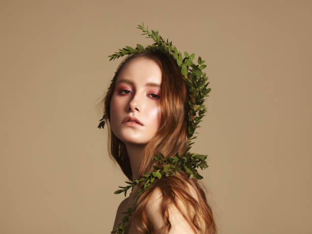 Beautiful young woman with leaves wreath Portrait of young natural woman with green leaves in her hair fine art portrait stock pictures, royalty-free photos & images