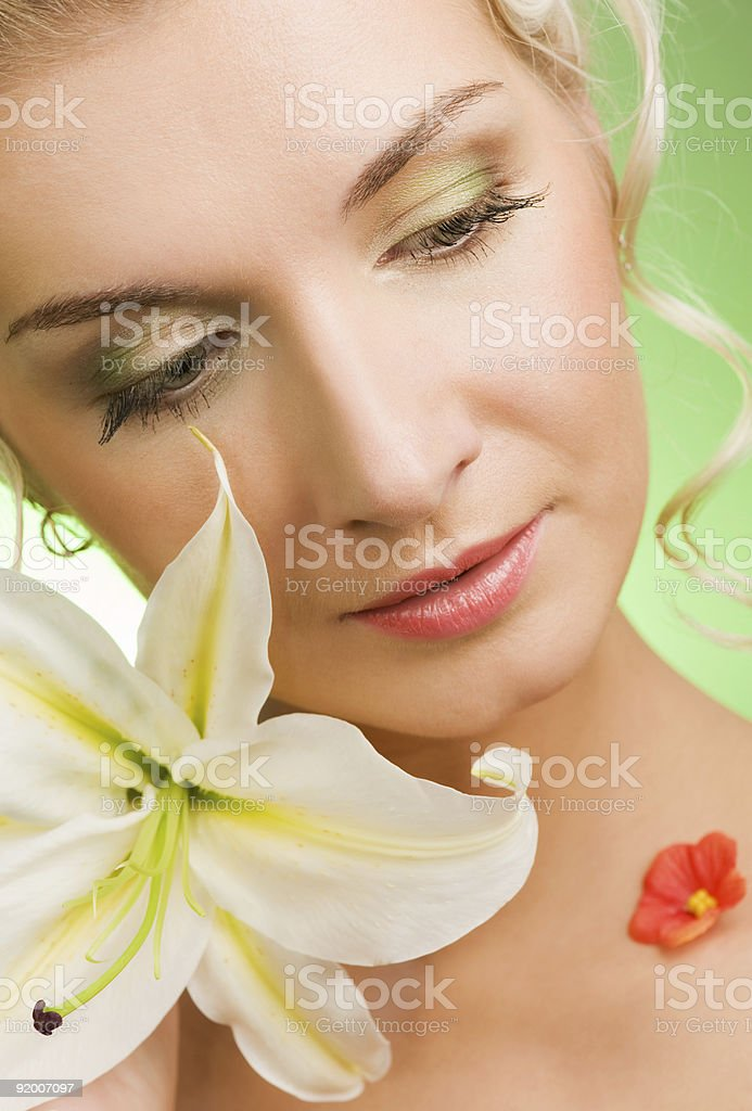 Beautiful young woman with lily flower. Close-up portrait royalty-free stock photo