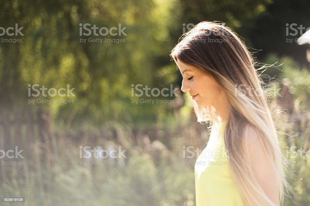 Beautiful young woman with long blonde hair. Sunny summer. stock photo