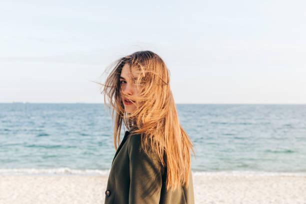 schöne junge frau mit langen braunen haar - lange jacken stock-fotos und bilder