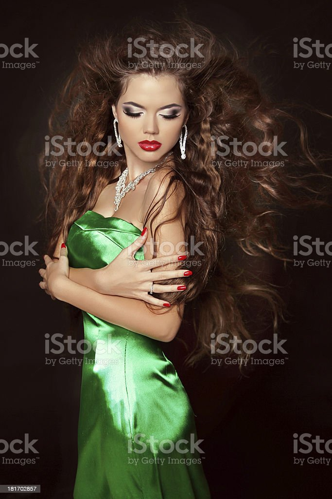 Beautiful young woman with long curly hairs in elegant dress royalty-free stock photo