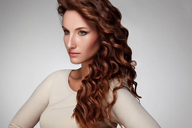 Beautiful young woman with long curly hairs stock photo
