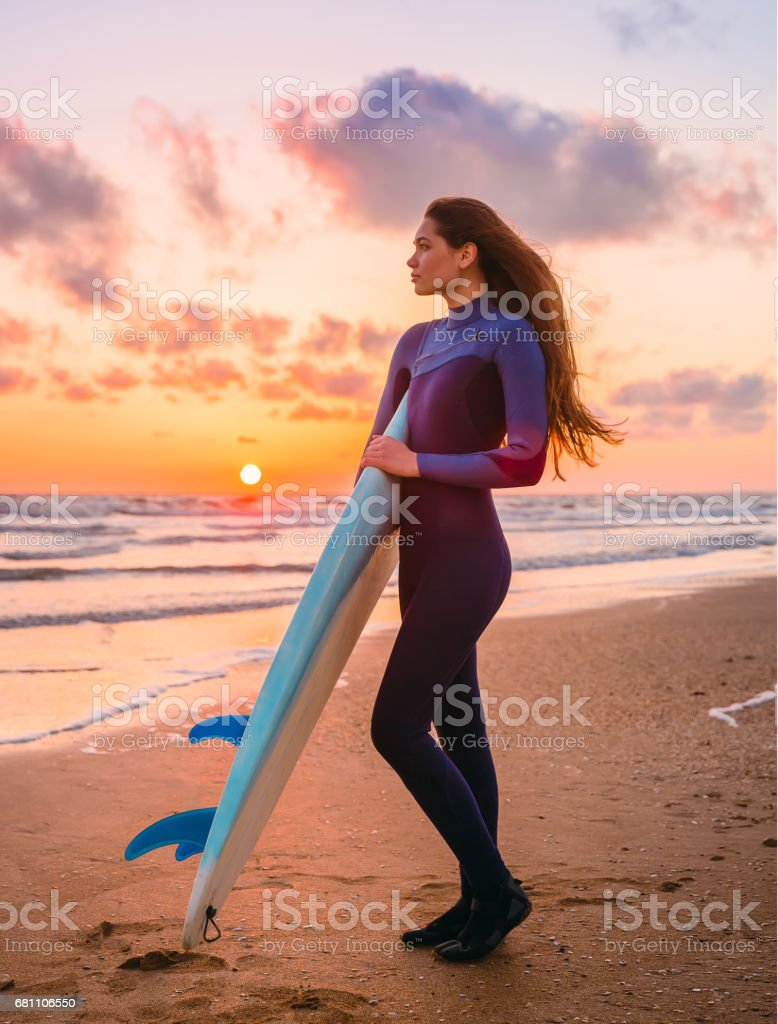 Beautiful young woman with long hair - surfer girl with surfboard on a beach at sunset or sunrise. Surf girl and ocean royalty-free stock photo