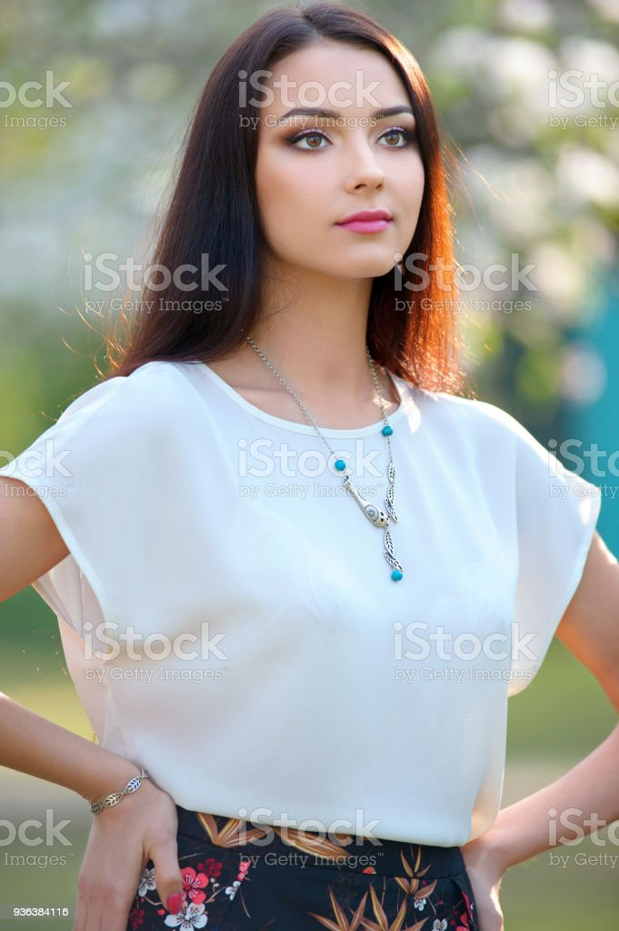 Beautiful young woman with long hair with a beautiful makeup and bracelet posing outdoors.  Around her neck is a stylish necklace. stock photo