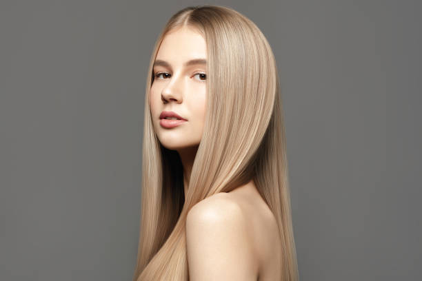 Beautiful young woman with long healthy hair posing against grey background. Beauty salon concept Beautiful young woman with long healthy hair posing against grey background. Beauty salon concept blond hair stock pictures, royalty-free photos & images