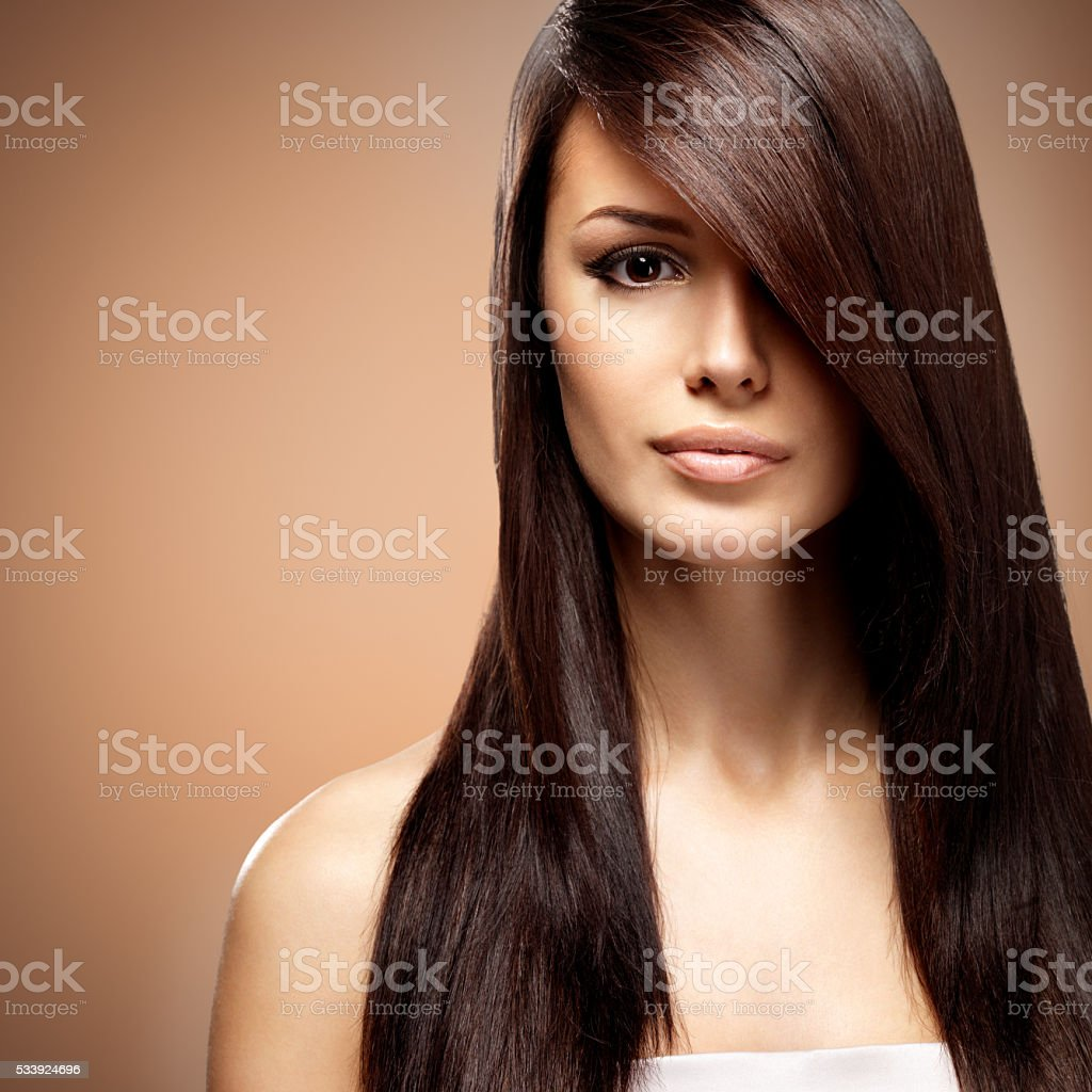 Beautiful young woman with long straight brown hair. stock photo