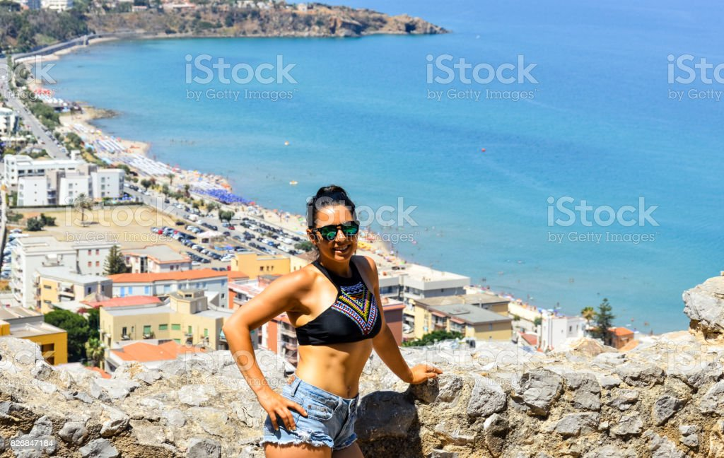 Beautiful young woman with Mediterranean coastline background - foto stock