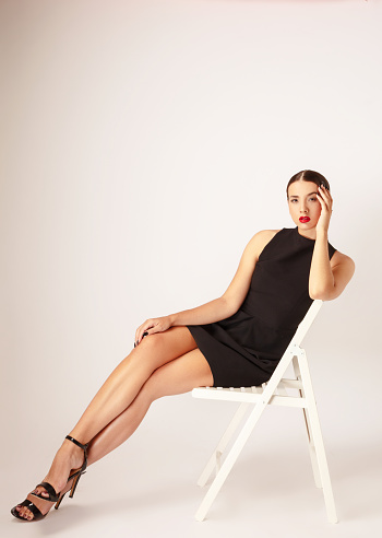 Beautiful young woman with mini black dress sitting on white chair front of white background.