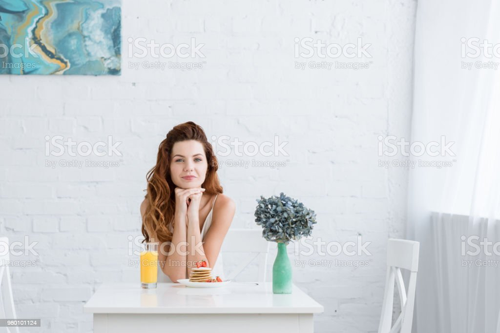 beautiful young woman with orange juice and pancakes with strawberry for breakfast at home looking at camera stock photo