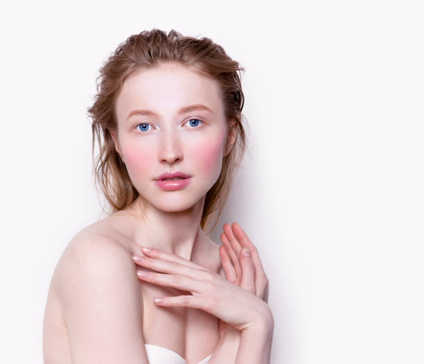 Beautiful young woman with pale white skin rose color blush cheeks and pink lipstick stock photo