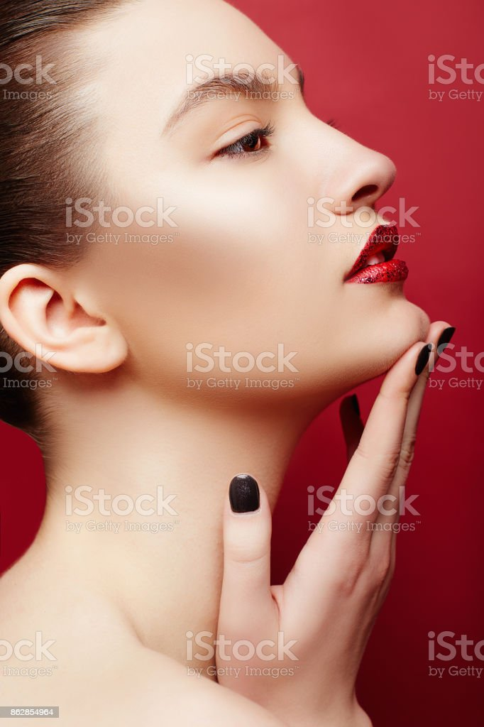 Beautiful Young Woman with perfect make-up and red lips. Beauty portrait of a gorgeous brunette women with clean skin. Red background. stock photo