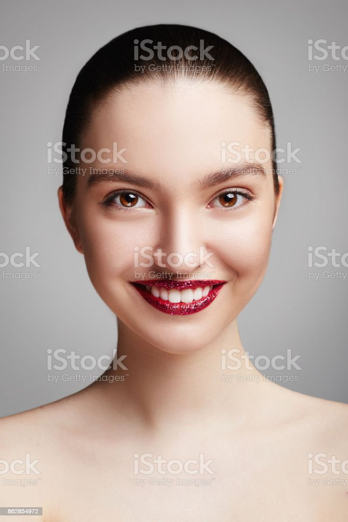 Beautiful Young Woman with perfect make-up and red lips. Beauty portrait of a smiling brunette women with perfect teeth. Grey background. stock photo