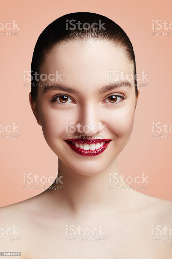 Beautiful Young Woman with perfect make-up and red lips. Beauty portrait of a smiling brunette women with perfect teeth. Beige background. stock photo