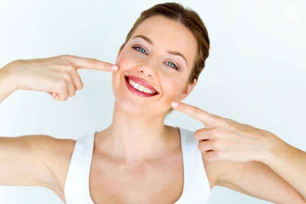 美麗的年輕女子與完美的笑容。隔離在白色。 - 露齒的笑容 個照片及圖片檔