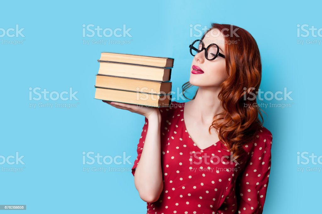 beautiful young woman with pile of books on the wonderful blue background stock photo