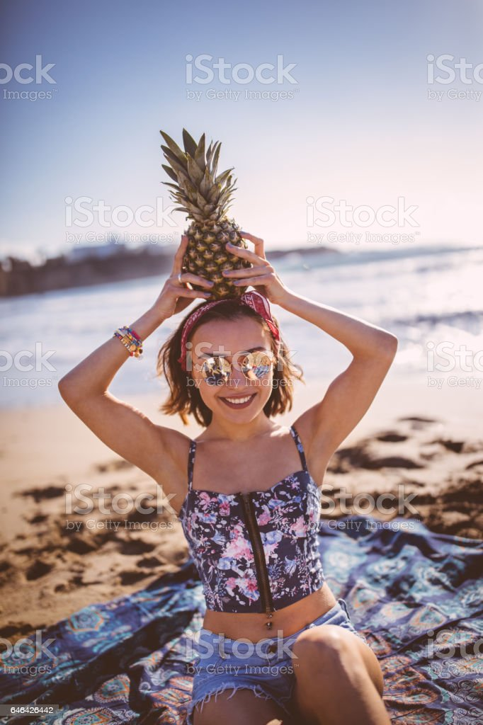 Beautiful young woman with pineapple at the beach stock photo