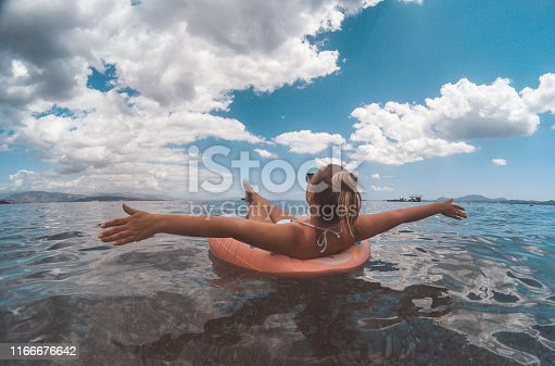 Beautiful young woman with inflationary donat on the seaside and enjoying summer time
