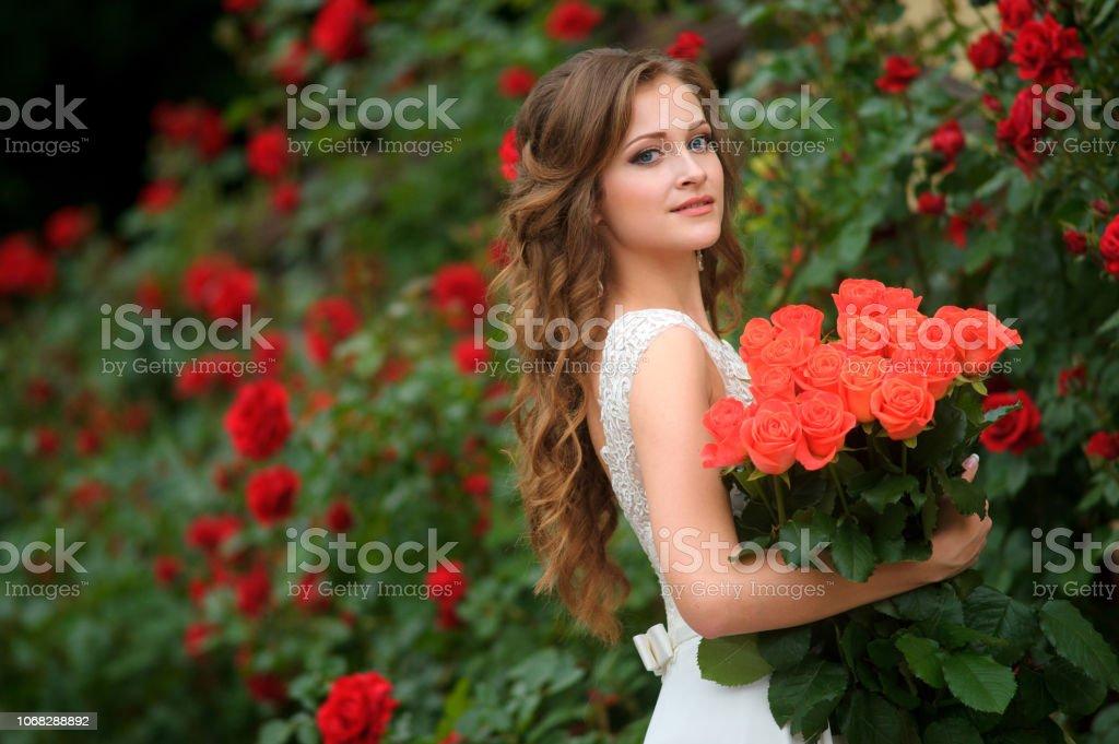 Hermosa Mujer Joven Con Flores Rojas Posando En El Jardín De ...