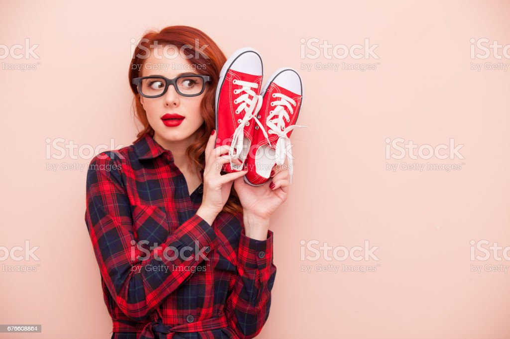 beautiful young woman with red gumshoes on the wonderful pink background stock photo