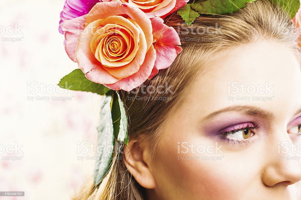 Beautiful young woman with roses in her hair stock photo