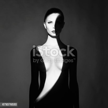 istock beautiful young woman with shadow dress on her body 679376530