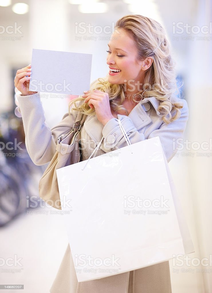 Beautiful young woman with shopping bags holding white card royalty-free stock photo