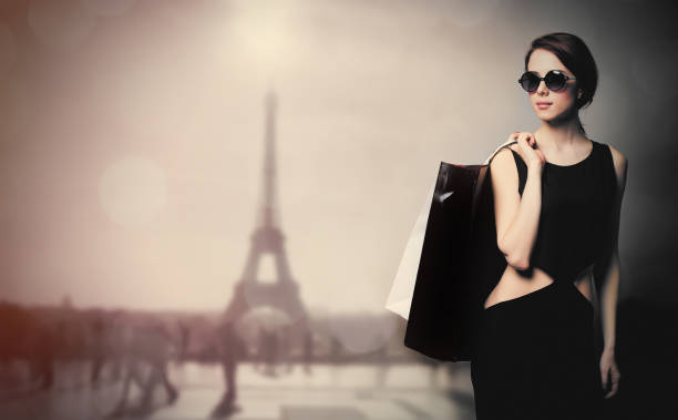 beautiful young woman with shopping bags on the wonderful eiffel tower background - mode paris photos et images de collection