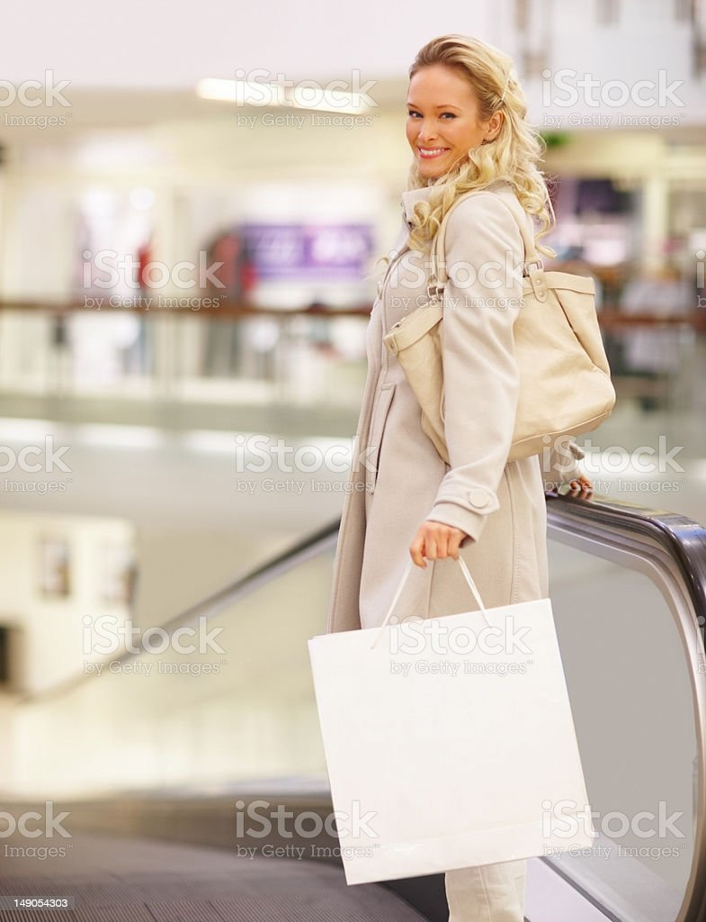 Beautiful young woman with shopping bags standing by escalator royalty-free stock photo