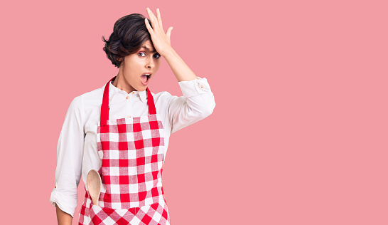 1046559700 istock photo Beautiful young woman with short hair wearing professional cook apron surprised with hand on head for mistake, remember error. forgot, bad memory concept. 1269296258