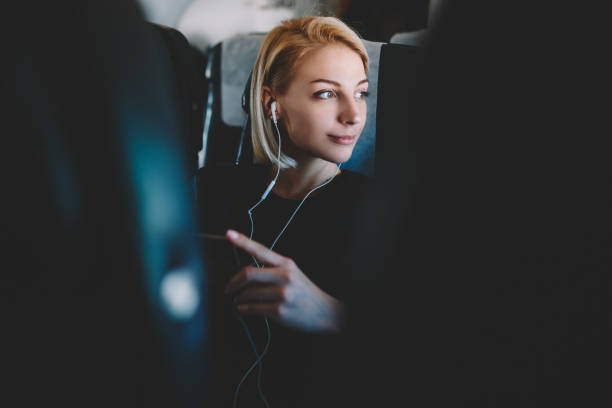 Beautiful young woman with short haircut listening favorite audio songs in modern earphones resting during flight and enjoying comfort first class sitting in seat on airplane board stock photo