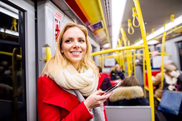 beautiful young woman with smart phone in subway train - winter austria train bildbanksfoton och bilder