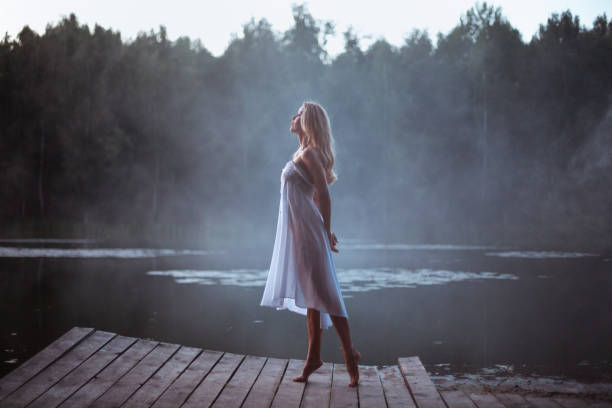 Beautiful young woman with sport body standing by the fogg lake at the dusk stock photo