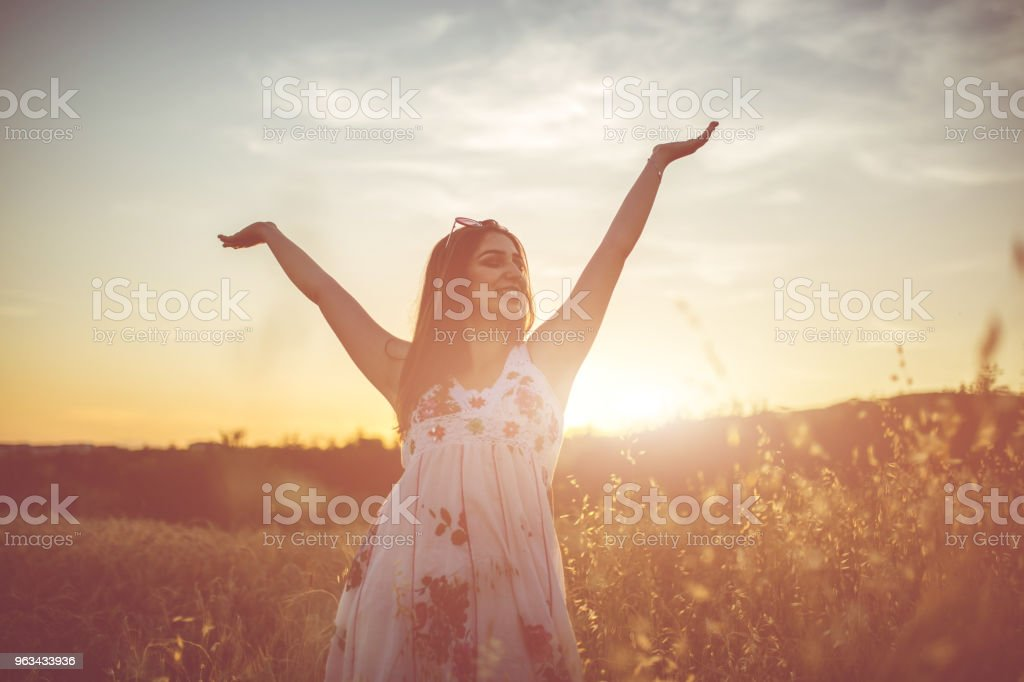 A beautiful young woman with spread hands in the wheat field. - Zbiór zdjęć royalty-free (20-29 lat)