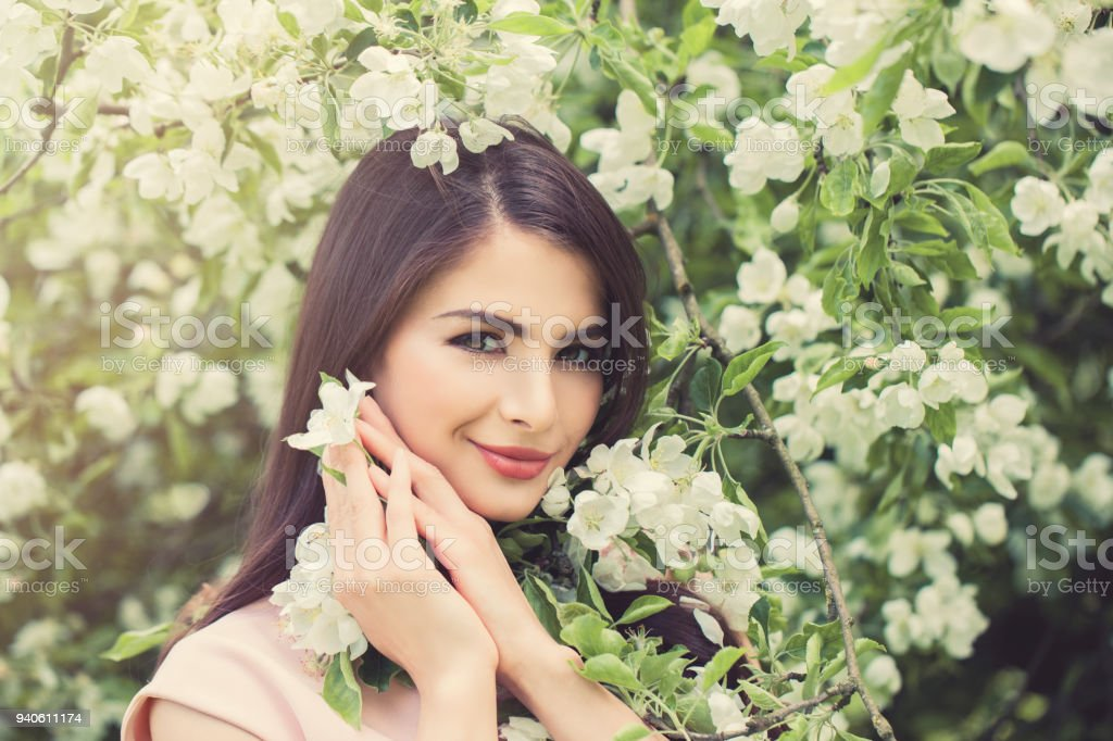 Beautiful Young Woman with Spring Flowers on Floral Spring Background, Female Face Closeup stock photo