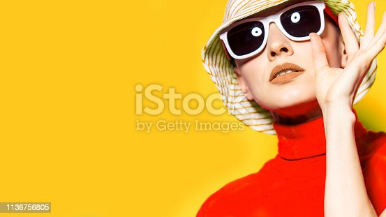 istock Beautiful young woman with sunglasses and hat 1136756805