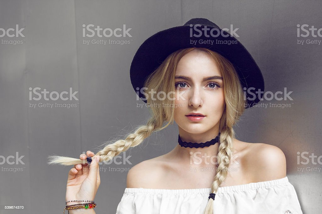 Close up of beautiful young blonde woman with black hat. Her hair is...