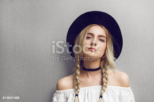 Close up of beautiful young  blonde woman with black hat. Her hair is tied in two big ponytails. Around neck she has black choker.