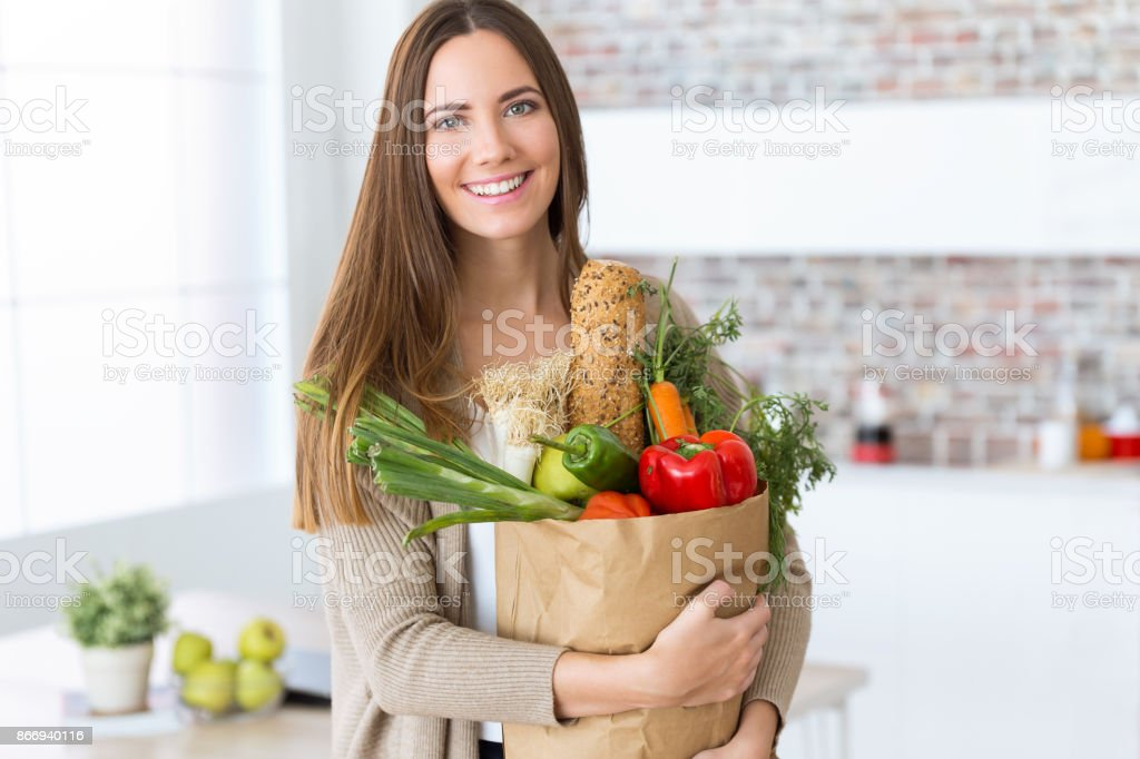 Beautiful young woman with vegetables in grocery bag at home. stock photo