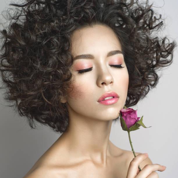 schöne junge frau mit violetten rose - soup_studio stock-fotos und bilder