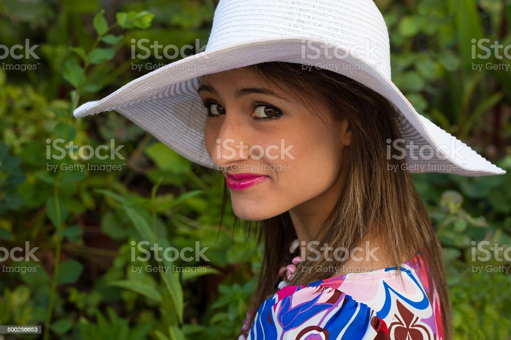Beautiful Young Woman With White Sun Hat in Her Garden stock photo