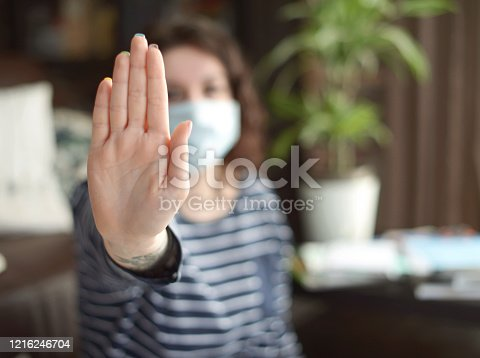 istock Beautiful young woman working at home ( in the mask) 1216246704