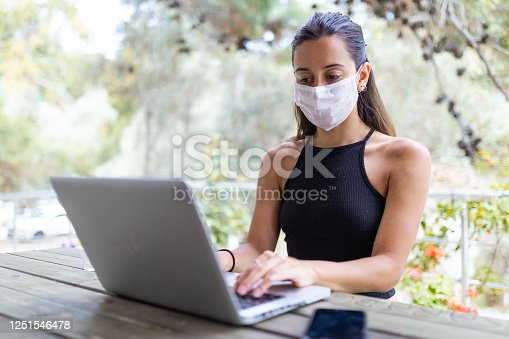 Beautiful young woman working on laptop with protection mask from the corona virus.